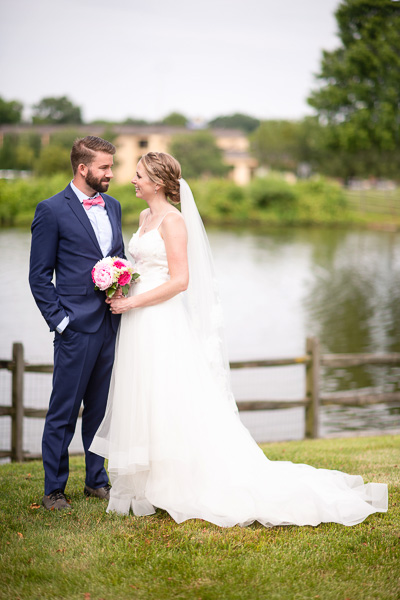 A bride and groom pose by the pond at the Hilton Christiana