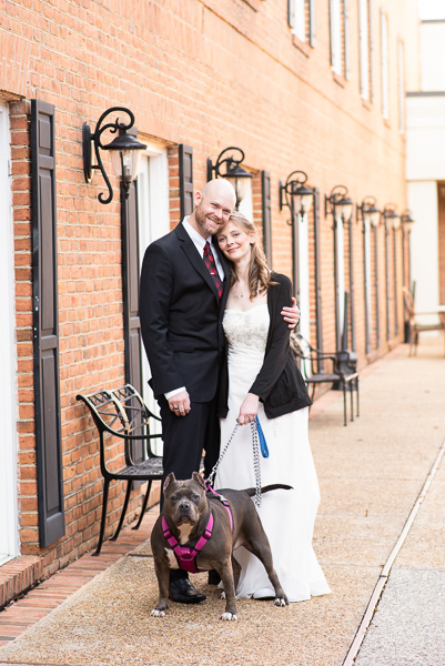 Couple poses in the courtyard with their dog