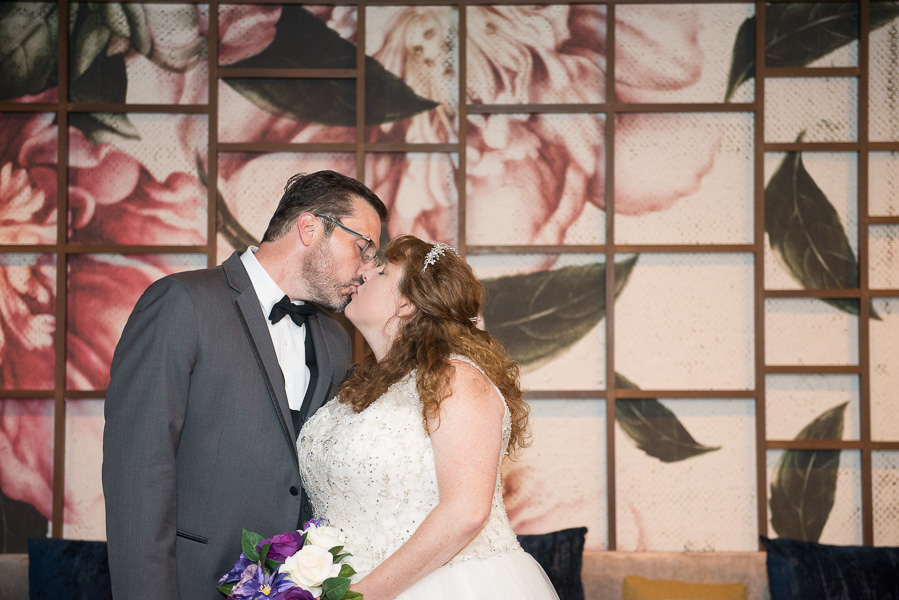 A couple kiss in front of a beautiful wall with painted flowers