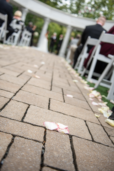 Close up of rose petals in aisle during Waterfall wedding ceremony