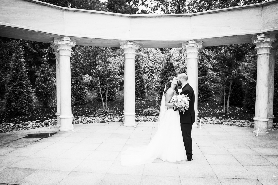 Black and white of bride and groom kissing at Waterfall wedding ceremony site