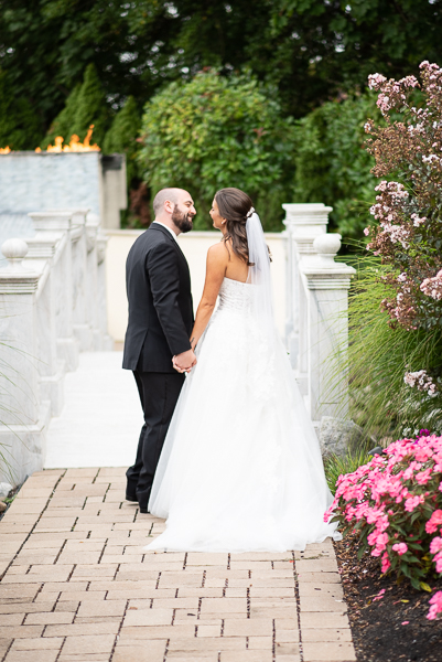 Wedding couple walk away from camera looking at each other