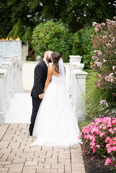 Bride and groom kiss in front of bridge at Waterfall Banquet Center in Delaware