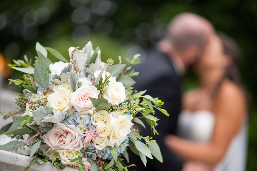 Close up of wedding flowers bride and groom kiss in background
