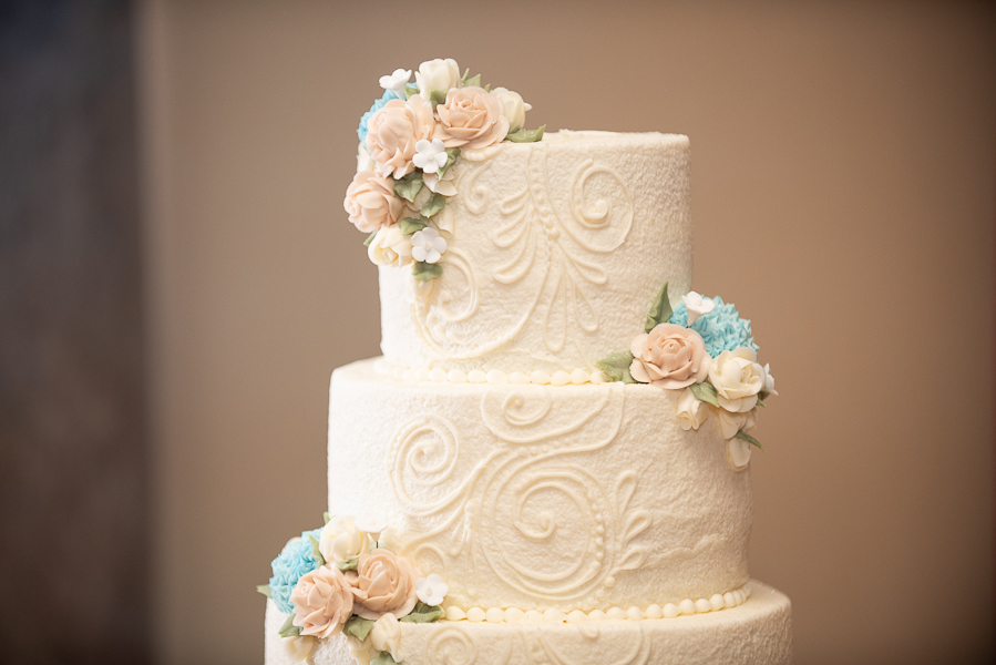 Close up of top part of wedding cake with icing roses and other flowers