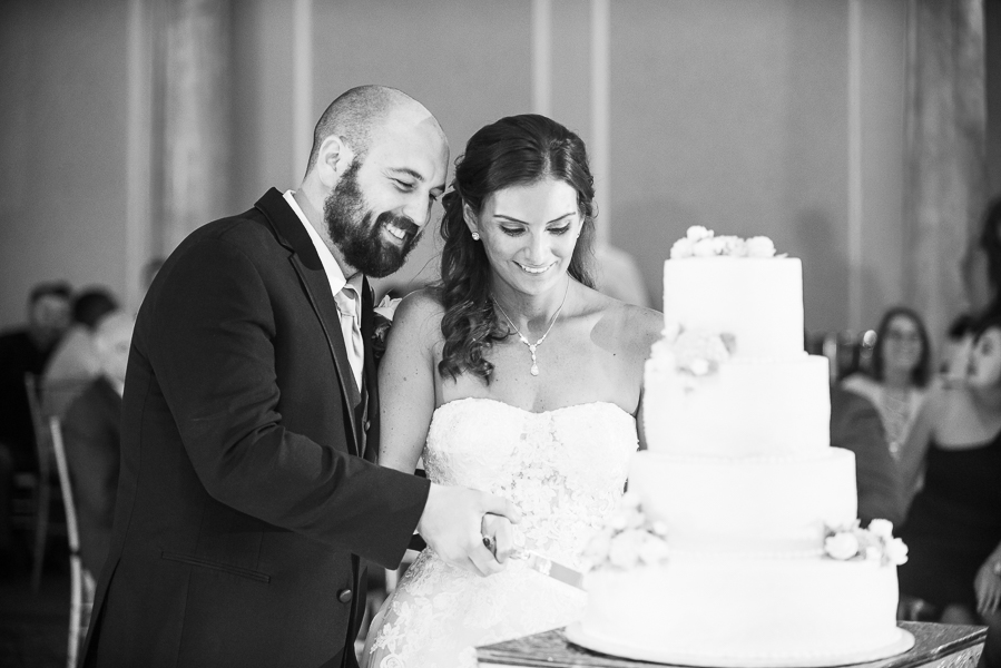 Black and white of the bride and groom cutting the cake