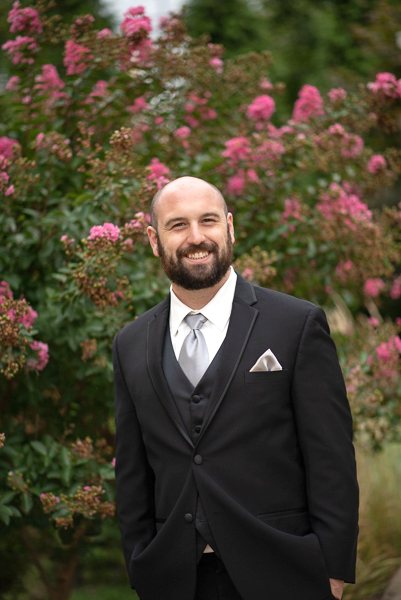 Groom portrait with pink flowering bush behind him