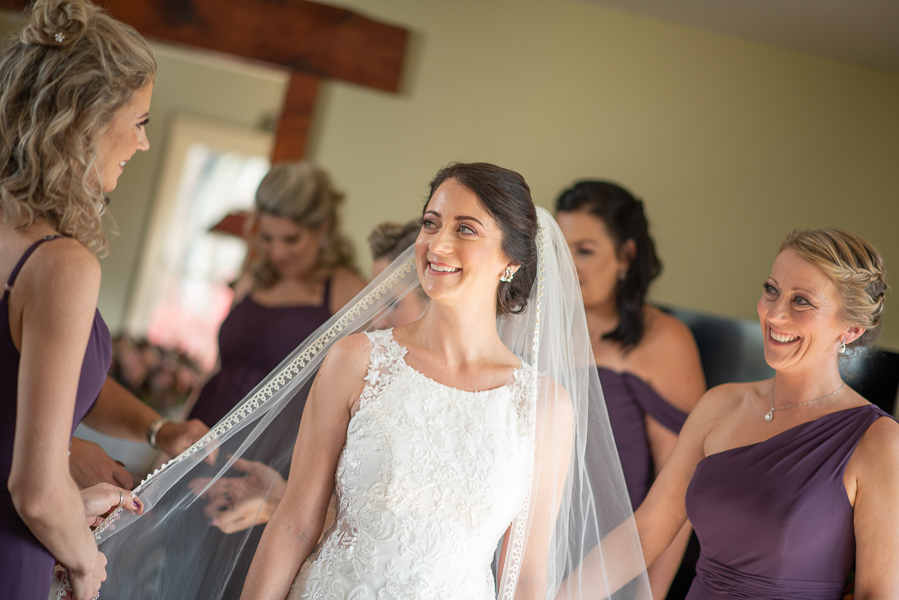 The bride smiles at her bridesmaids as they help her with her veil