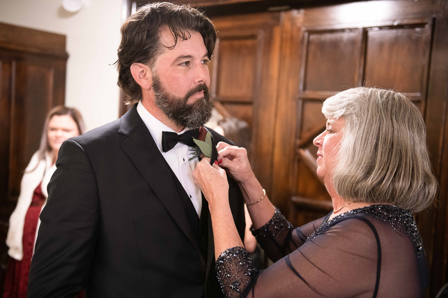 Mother of the groom puts boutonniere on her son