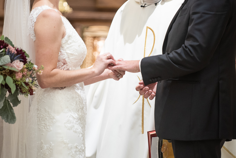 Close up of bride placing wedding ring on groom's finger