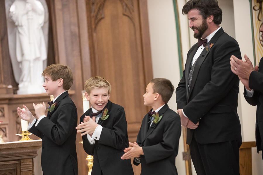 Groom's young son smiles and claps as the couple is announced husband and wife