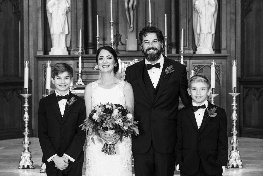 Black and white family portrait in the church of bride and groom and the groom's sons