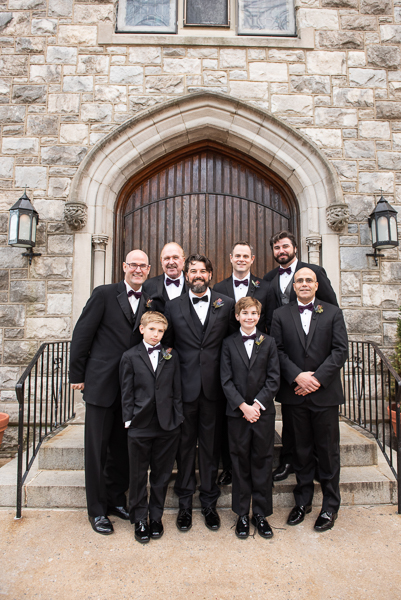 Groom poses with groomsmen outside on church steps before heading to The Farmhouse in Delaware