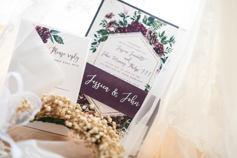 Wedding invitation closeup (reception at The Farmhouse in Delaware) with dried baby's breath and veil