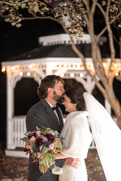 Night shot in front of the gazebo of a groom kissing his bride's forehead at The Farmhouse in Delaware