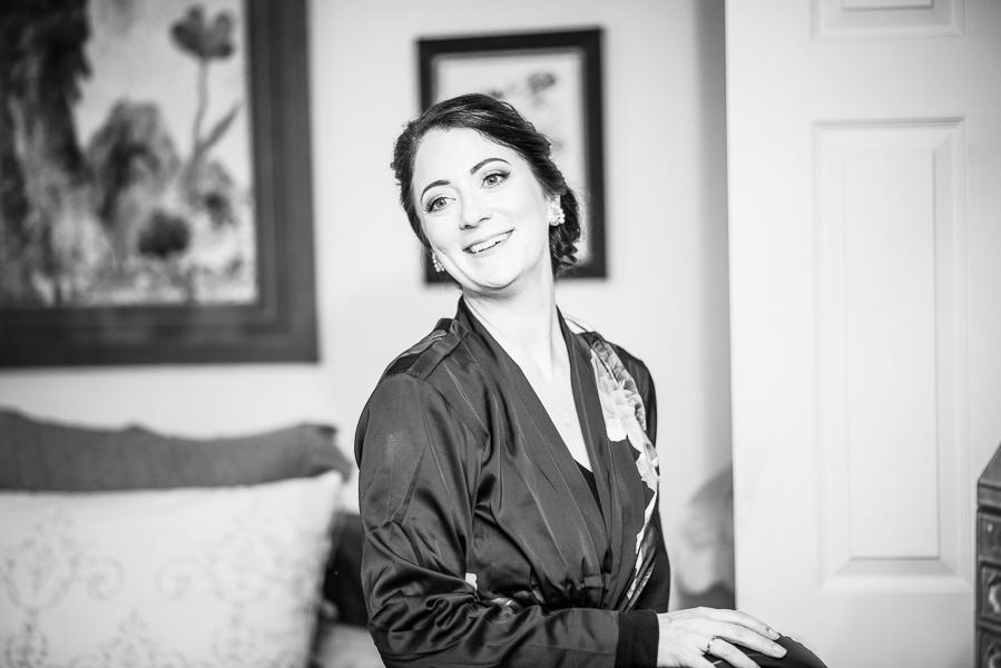 Black and white of the bride in a robe getting ready for her ceremony