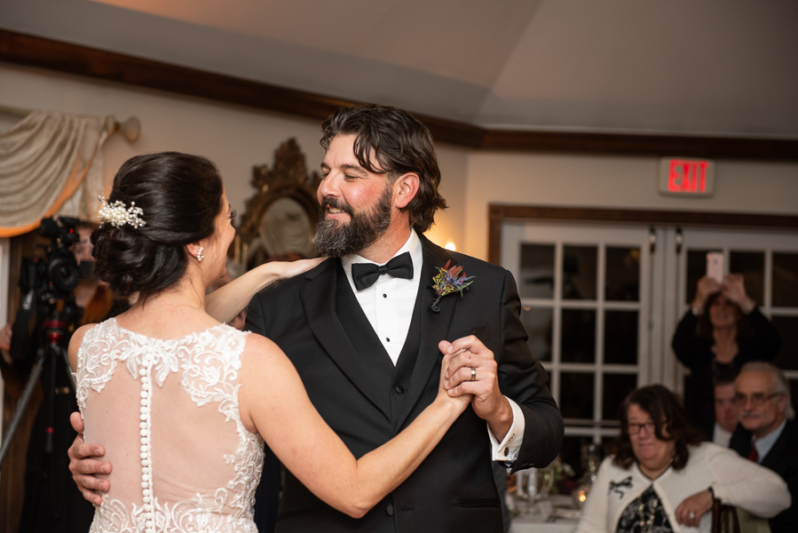 The groom smiles at the bride during their first dance at The Farmhouse in Delaware