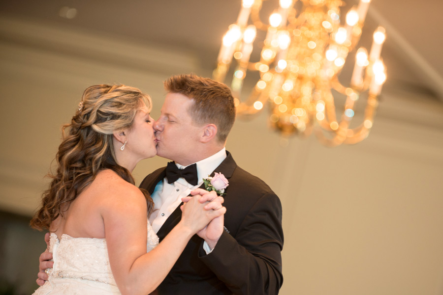 Bride and groom kiss during first dance with chandelier in background