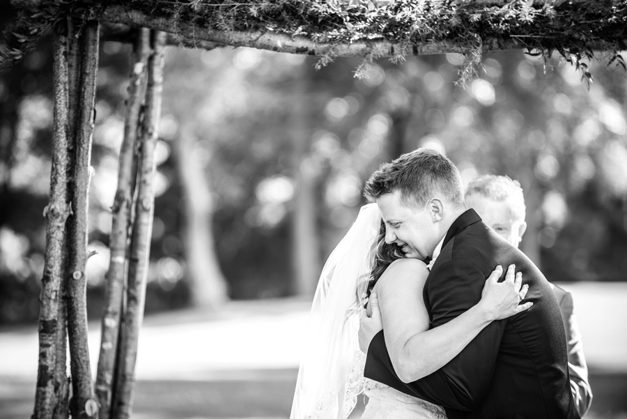 Black and white of bride and groom embracing after outdoor ceremony at Deerfield in Newark, Delaware