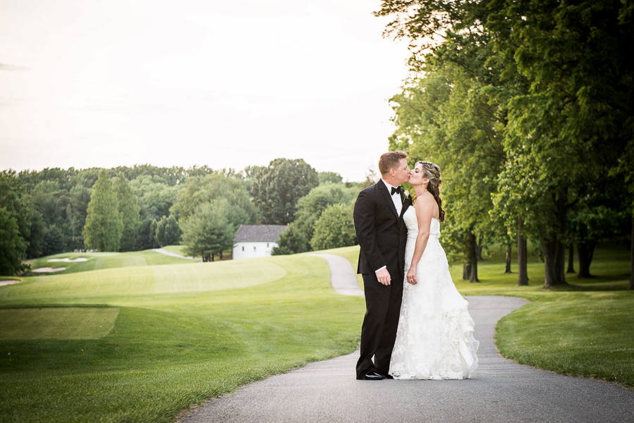 Bride and groom kiss outside on beautiful grounds of Deerfield in Newark Delaware