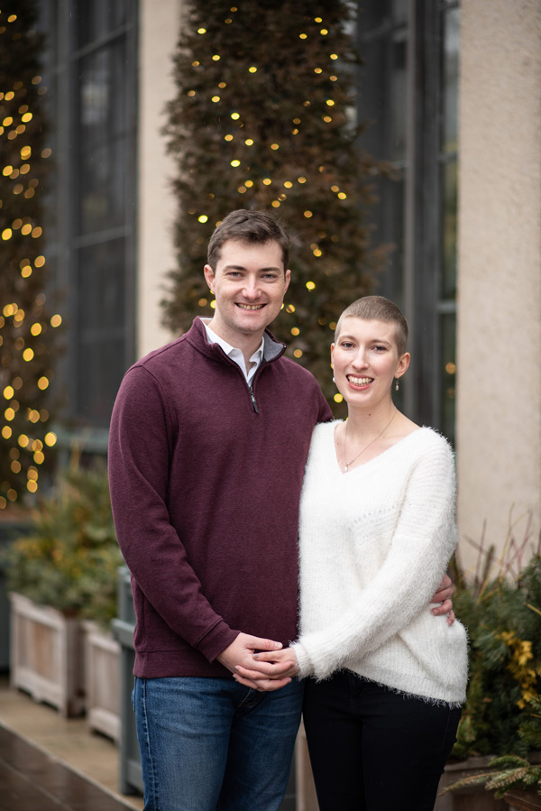 Couple smiles at the camera with Christmas lights behind them