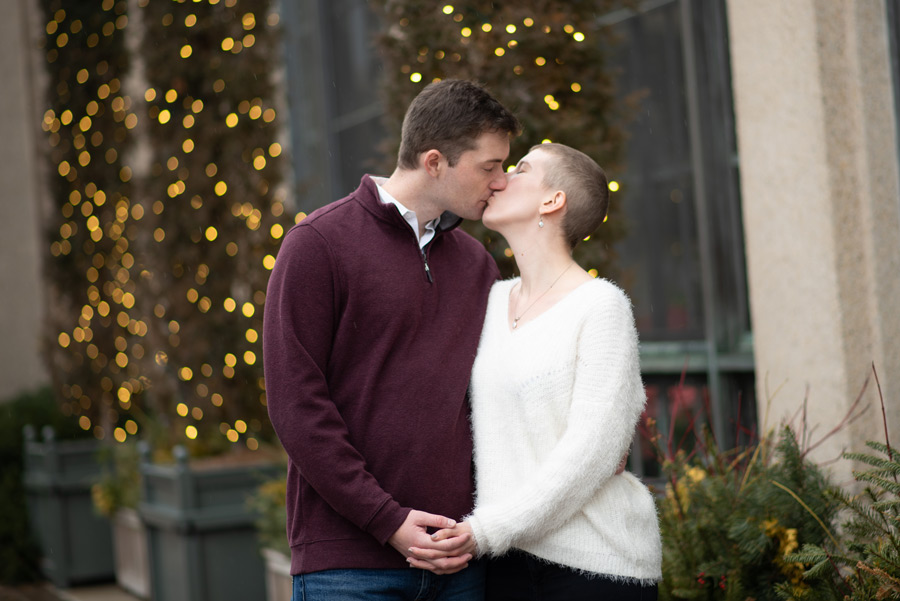 Engaged and kissing at Longwood Christmas outside greenhouse