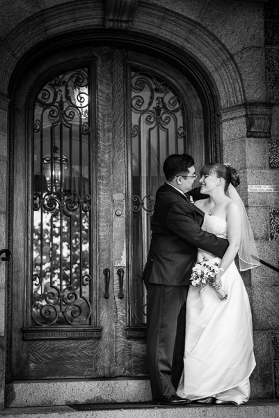 Bride and groom stand looking at each other in front of ornate wooden doors