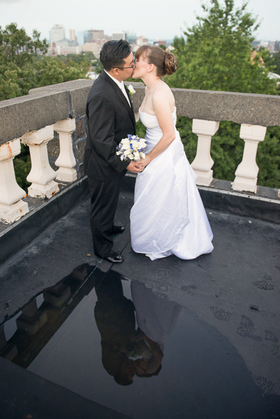 Couple kisses on a rooftop turret and their reflection is seen in a rooftop puddle