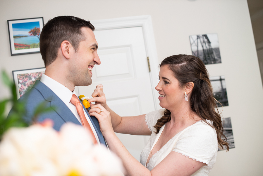 Bride puts boutonniere on groom before intimate Delaware ceremony