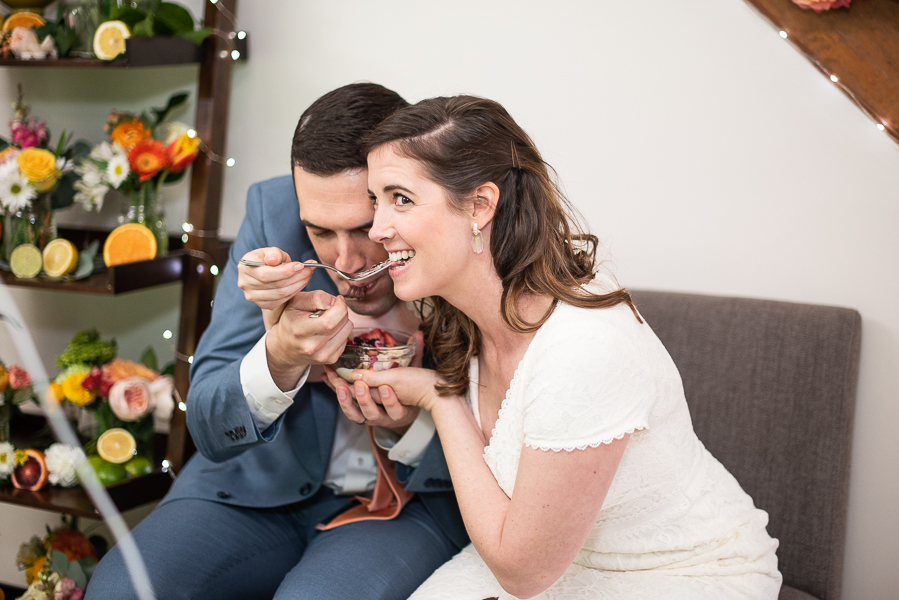 Bride and groom feed each other at intimate Delaware wedding