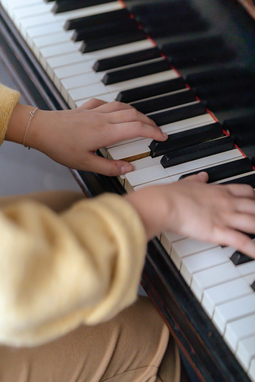 unrecognizable female musician playing melody on piano in room