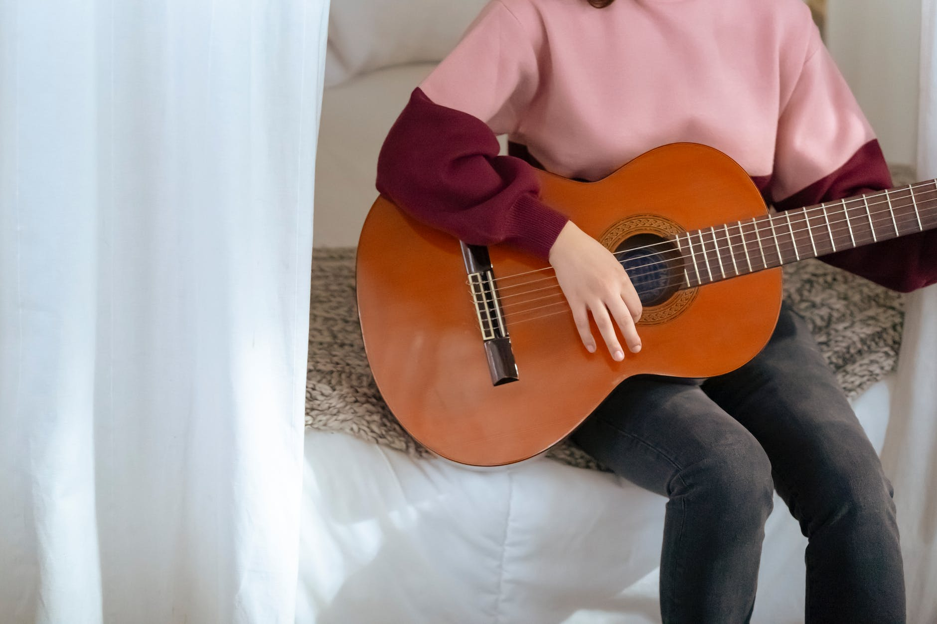 crop woman playing guitar on bed