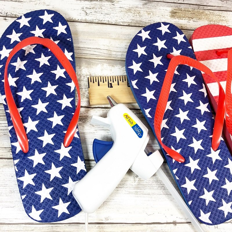 Layout seven flip flops, two blue with white stars and five red with white stripes on work surface. Measure and cut a yardstick to fit and glue to the back of the flips flops Creatively Beth #creativelybeth #flipflopsign #freedom #recycle #upcycle #dollartree #craft