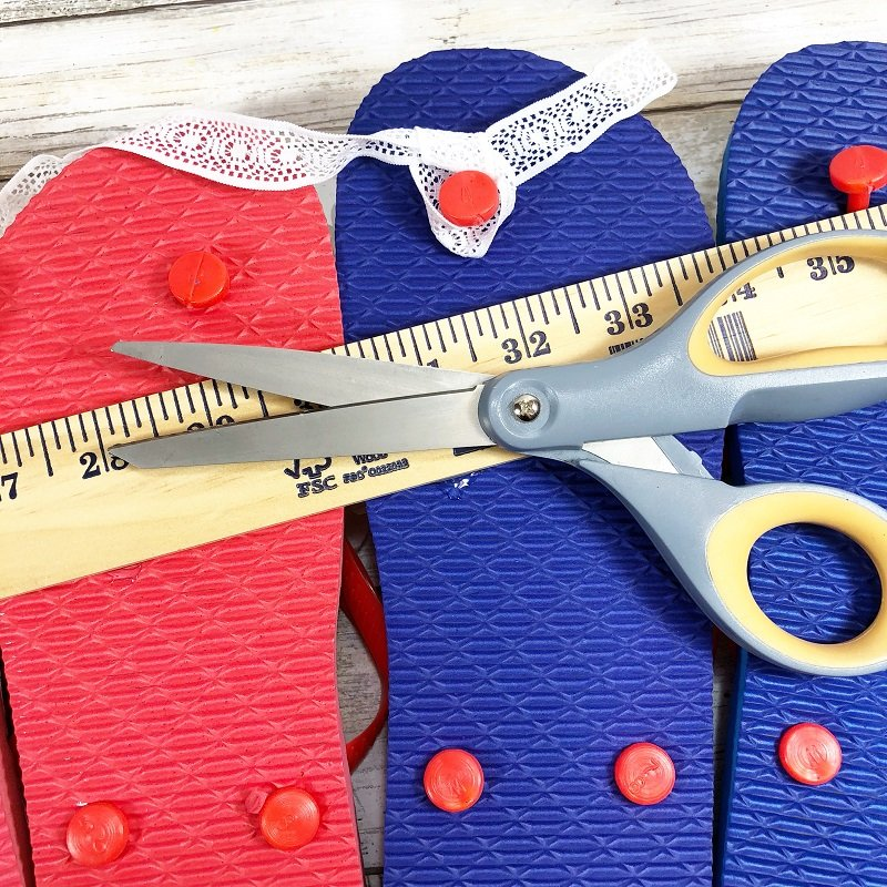 Measure and cut a length of white ribbon and tie to the button on the back of the flip flop to create a hanger Creatively Beth #creativelybeth #flipflopsign #freedom #recycle #upcycle #dollartree #craft