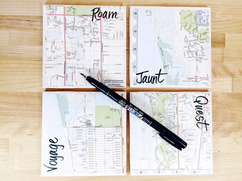 Hand letter travel words onto map covered coasted with Fudenosuke Brush Pen Creatively Beth #creativelybeth #upcycled #recycled #crafts #maps