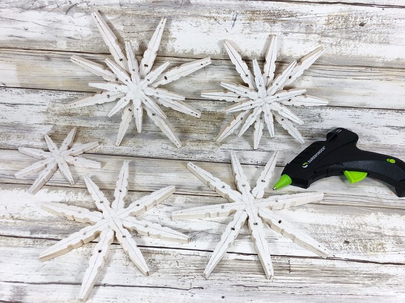 Layer small clothespin snowflakes onto larger ones and leave some plain Craft Creatively Beth #creativelybeth #christmasinjuly #christmasornament #dollartreecraft #snowflake #clothespin