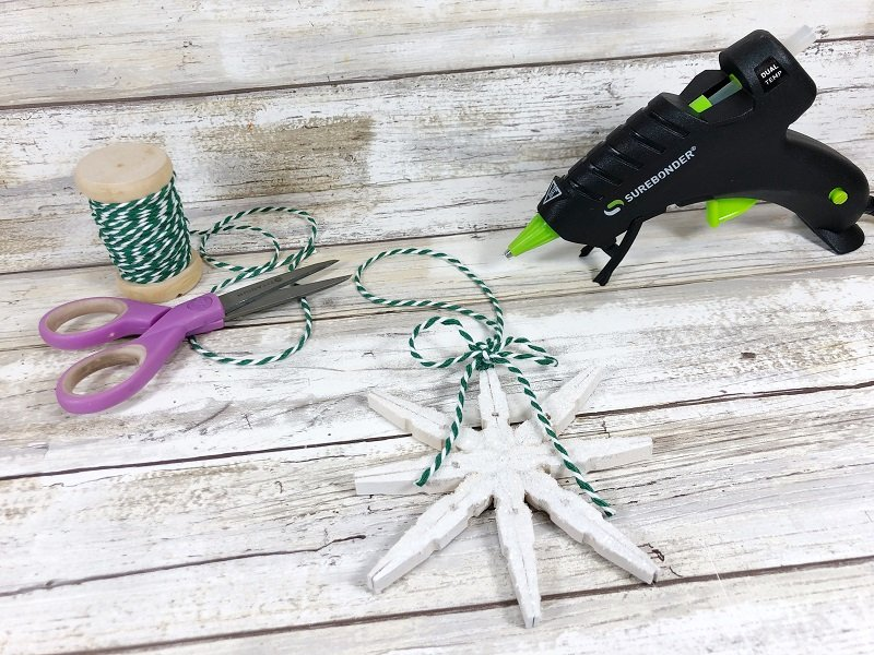 Attach a bakers twine or ribbon hanger to the clothespin snowflakes Craft Creatively Beth #creativelybeth #christmasinjuly #christmasornament #dollartreecraft #snowflake #clothespin