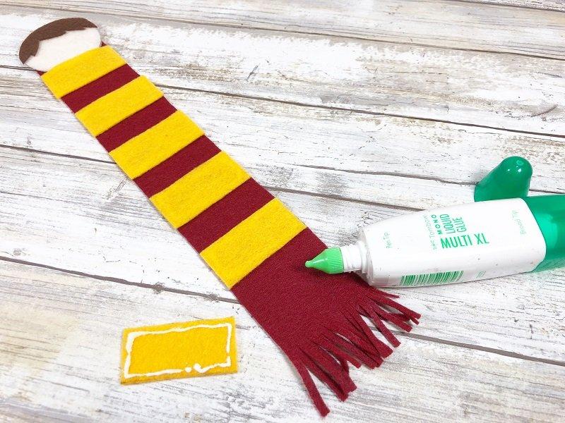 Glue gold stripes onto the burgundy scarf Creatively Beth #creativelybeth #harrypottercrafts #harrypotter #feltcrafts #kidscrafts