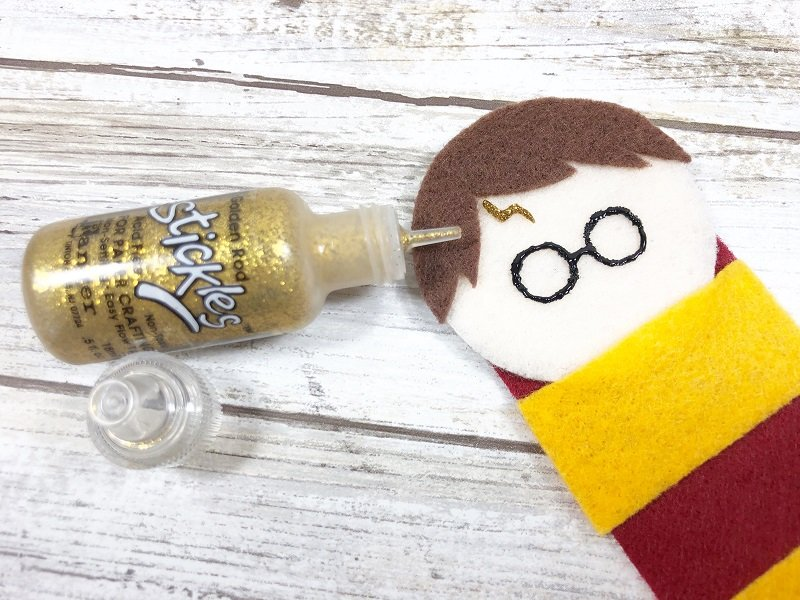 Add Harry's lightning bolt shaped scar on his forehead with gold glitter glue Creatively Beth #creativelybeth #harrypottercrafts #harrypotter #feltcrafts #kidscrafts