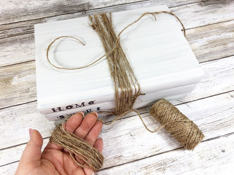 To create a bow wrap twine aroung your hand a dozen times Creatively Beth #creativelybeth #dollartreecraft #homedecor #bookstack #diy