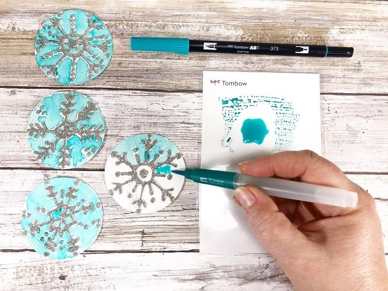 Watercolor around the glittered snowflakes with Dula Brush Pens and the Tombow Water Brush Creatively Beth #creativelybeth #tombow #handlettered #glitter #banner #adhesives