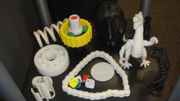 Models of chains, gears, wheels, and even a dinosaur are made at the touch of a button on the using the Dimension 1200es 3D printer at Braintree Printing in Braintree, Massachusetts.