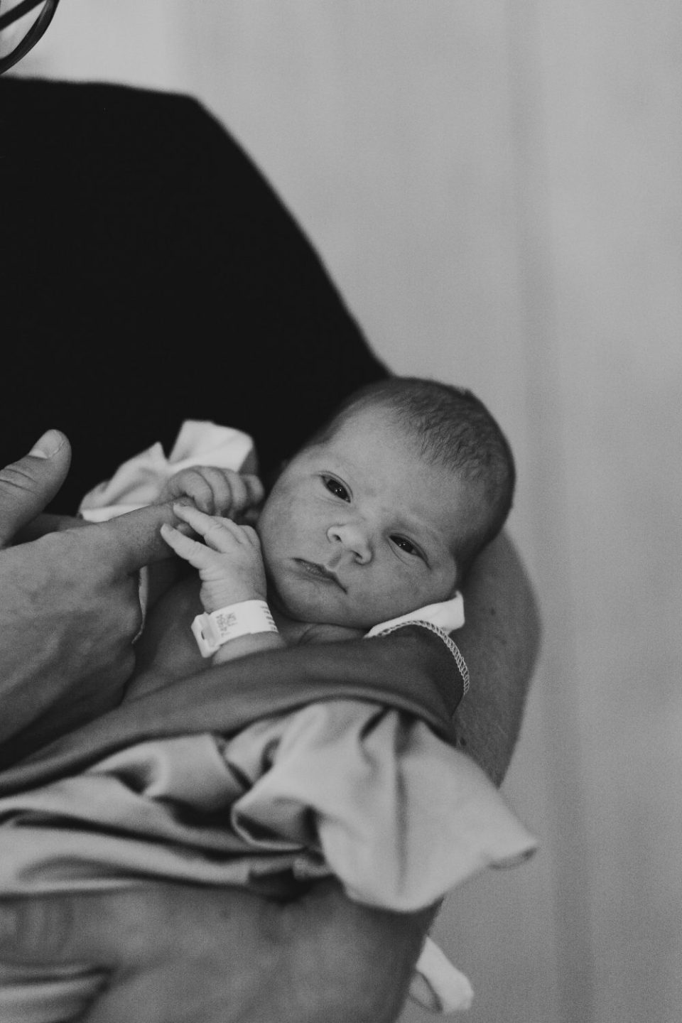 Dad holding newborn baby in birth photography at hospital