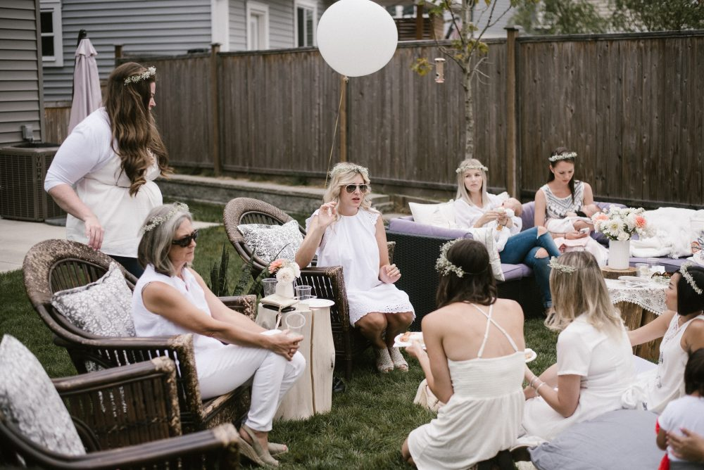 Guests gathered together at all white baby shower