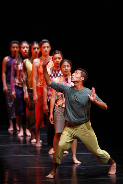 A line of 7 youth dancers, one in front of another on a stage. All are barefoot and female, except for a single male in the front of the line, gesturing with both arms extended outward. Photo courtesy of The Wooden Floor True in Irvine Barclay Theatre in Irvine, CA. Photo by Kevin P. Casey.