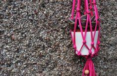 pink macrame hanging planter against pebbledash