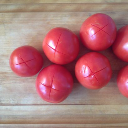 Cut crosses in bottom of Tomatoes