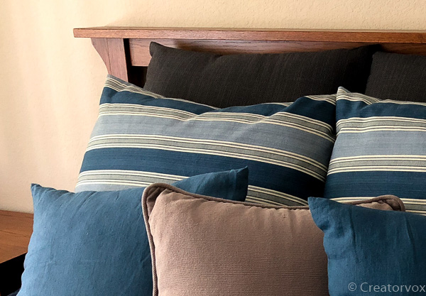 pillow covers of various sizes decorate a bed