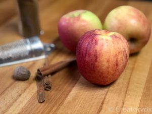 apples sitting on a counter with cinnamon and nutmeg