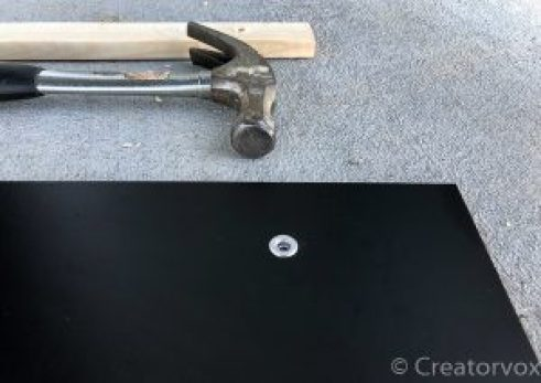 grommet installed in organization board with hammer and backing-board